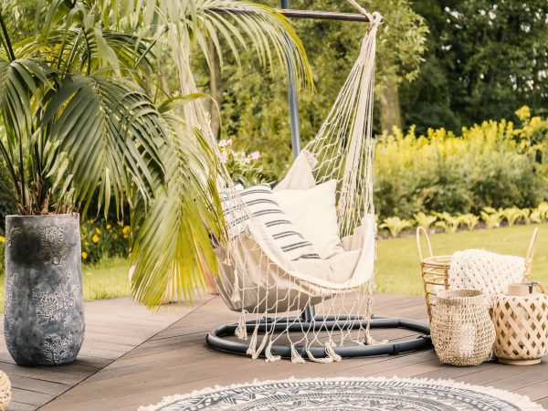Summer in the green garden with a hammock and a palm tree on a terrace.