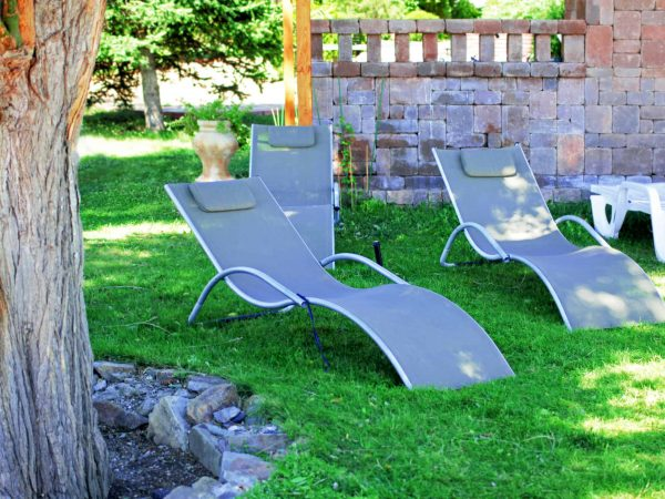 Grey fabric sun loungers in green summer garden
