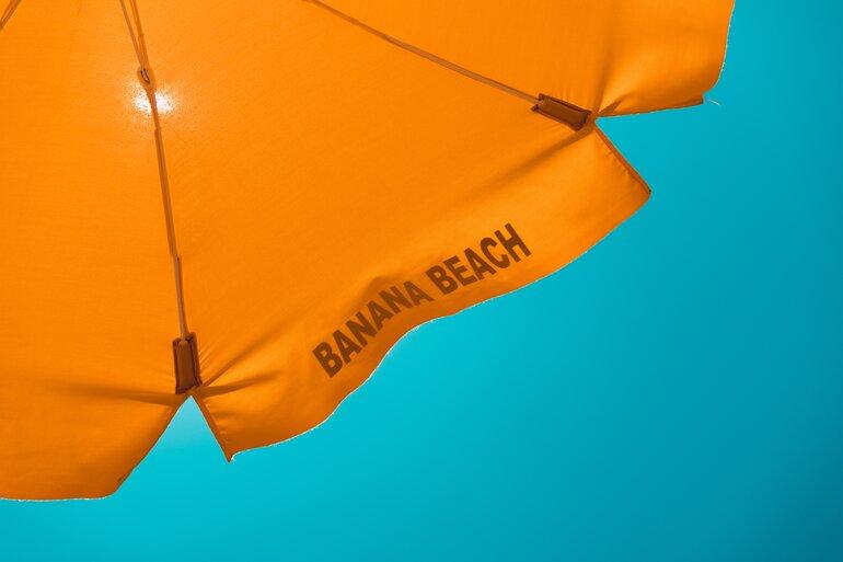 orangener Schirm vor hellblauem Himmel