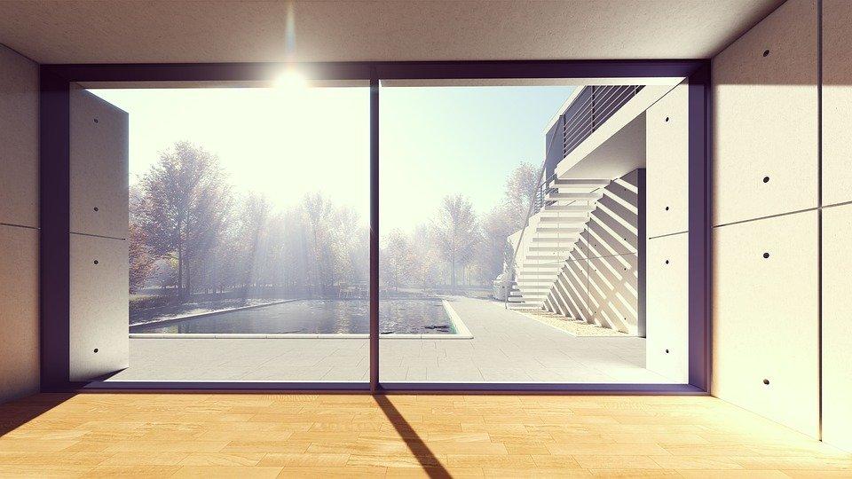 Sonne strahlt durch ein großes Fenster in einen Raum.